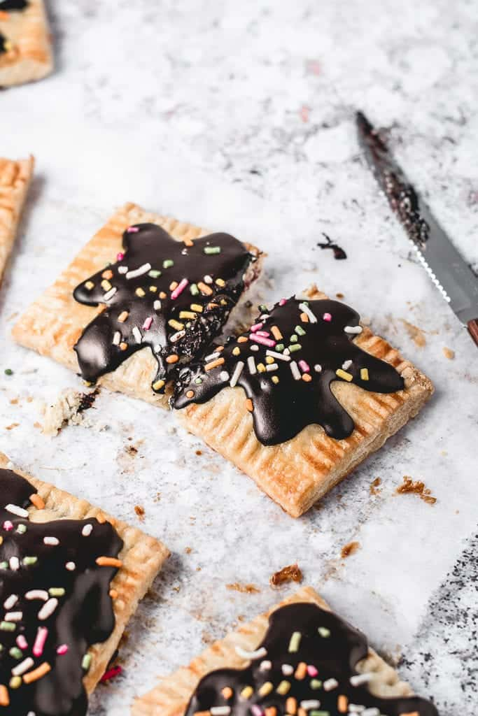 These Cherry Pop Tarts with sprinkled Chocolate glaze are a perfect snack. Sweet and tangy cherry filling, cloaked in flaky, all-butter pie crust and then topped with simple chocolate glaze - heavenly combination! Ooh, let's not forget sprinkles! ⎪www.anasbakingchronicles.com