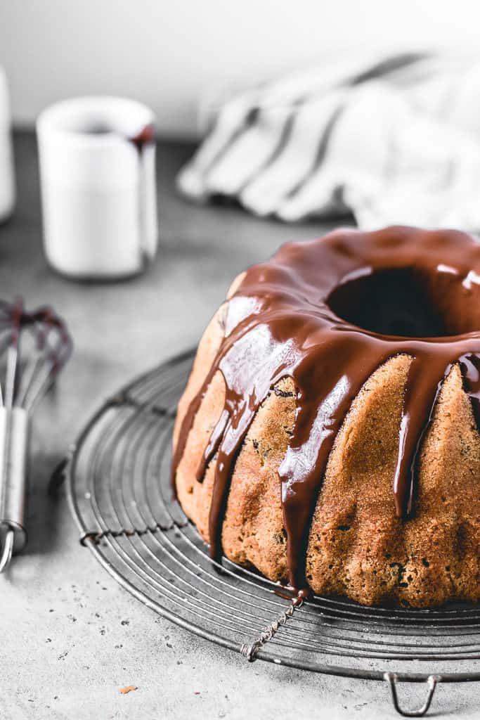 This Chocolate Chip Pumpkin Bundt Cake is a perfect fall treat! Incredibly moist and delicious pumpkin spice cake with chocolate chips and covered in decadent chocolate glaze.⎪www.anasbakingchronicles.com