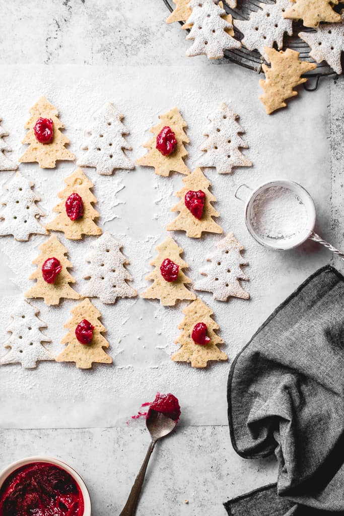 These lovely Pistachio Cranberry Linzer Christmas trees are going to be the star of your holiday table! With their festive looks and delicious flavour, they will win everyone's heart! ⎪www.anasbakingchronicles.com  #christmascookies #christmasbaking #linzercookies