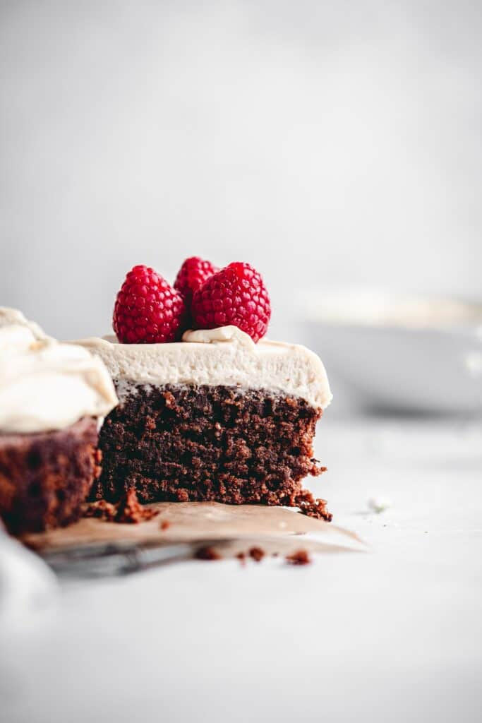 Slice of flourless and gluten free chocolate cake with Irish cream mascarpone frosting, decorated with raspberries.