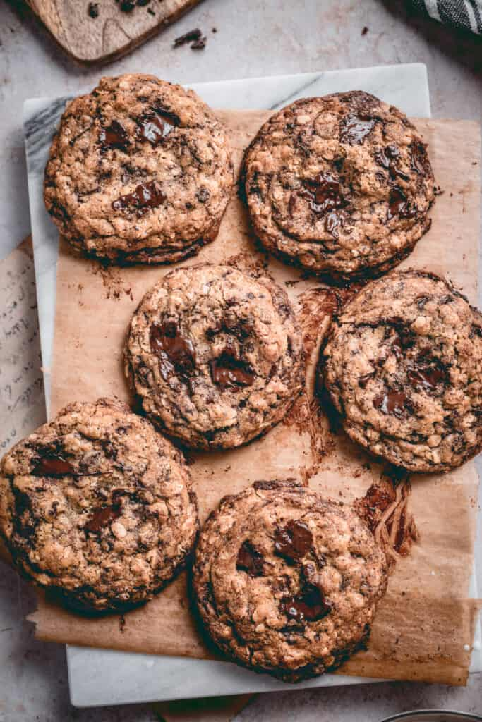 Freshly baked oatmeal chocolate chip cookies on a baking paper, placed on a marble board.