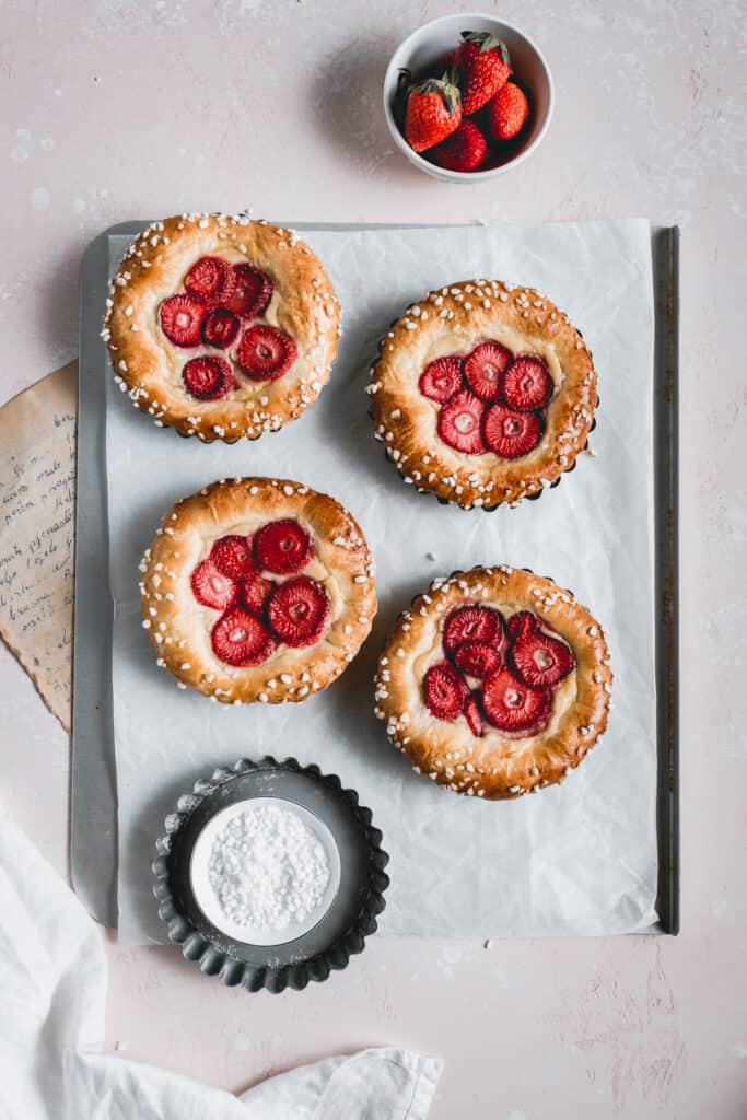Brioche tarts made with tonka bean pastry cream and strawberries placed on a baking tray.