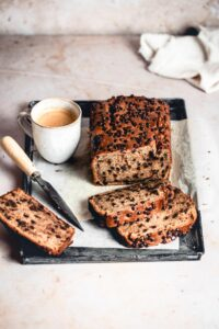 Peanut Butter Chocolate Chip Banana Bread on a tray, with a few cut slices, knife and a cup of coffee.